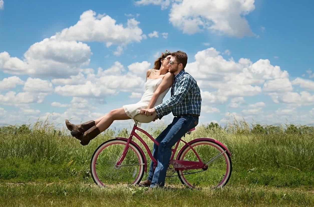 Couple sur un vélo dans un champ